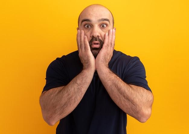 Bebaarde man in marineblauw t-shirt verbaasd en verrast staande over oranje muur