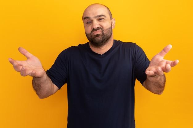 Bebaarde man in marineblauw t-shirt verward en ontevreden met opgeheven armen boven de oranje muur