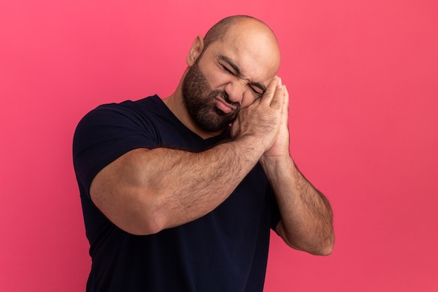 Bebaarde man in marineblauw t-shirt wil slapen slaapgebaar maken handpalmen tegen elkaar houden leunend hoofd op handpalmen staande over roze muur