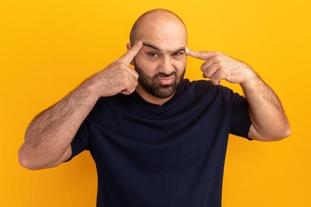 Bebaarde man in marineblauw t-shirt wordt verward wijzend met wijsvingers naar zijn slapen die over oranje muur staan