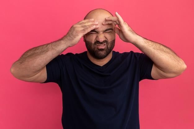 Bebaarde man in marineblauw t-shirt ziet er onwel uit en raakt zijn hoofd aan met een geërgerde uitdrukking die lijdt aan sterke hoofdpijn die over roze muur staat