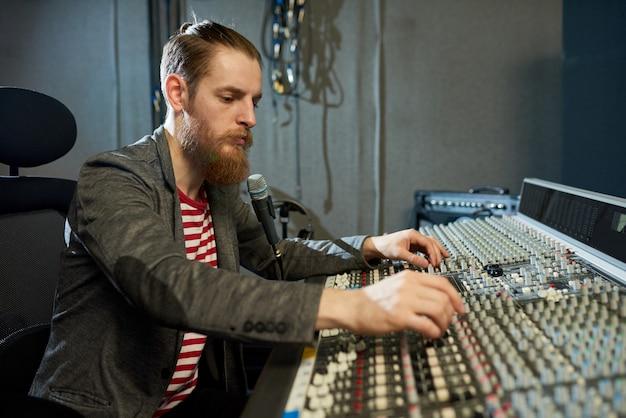 Bebaarde man in muziek opnamestudio