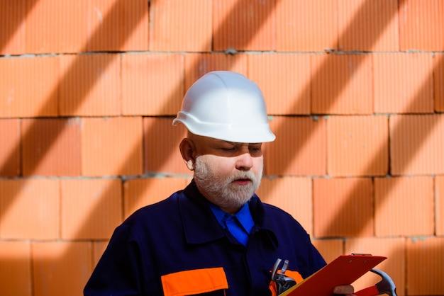 Bebaarde man in pak met bouwhelm bouwvakker in veiligheidshelm bouwsector