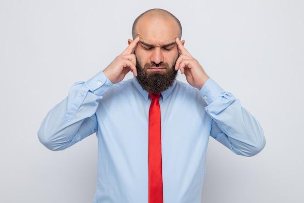 Bebaarde man in rode stropdas en blauw shirt die zijn slapen aanraakt met vingers die zich onwel voelen en lijden aan hoofdpijn