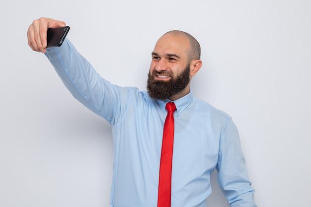 Bebaarde man in rode stropdas en blauw shirt doet selfie met smartphone glimlachend vrolijk gelukkig en positief