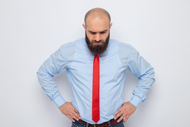 Bebaarde man in rode stropdas en blauw shirt kijkt verbaasd naar beneden met handen op heup
