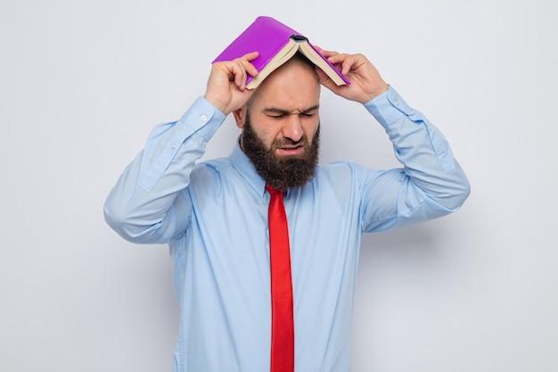 Bebaarde man in rode stropdas en blauw shirt met boek boven zijn hoofd en ziet er moe en geïrriteerd uit