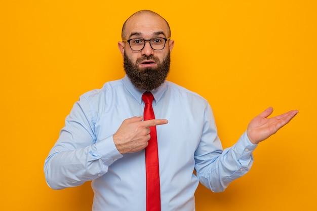Bebaarde man in rode stropdas en blauw shirt met bril kijkend naar camera met zelfverzekerde glimlach presenteren met arm van haar hand wijzend met wijsvinger naar haar hand staande over oranje achtergrond