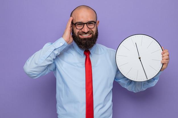 Bebaarde man in rode stropdas en blauw shirt met bril met klok kijkend naar camera blij en opgewonden glimlachend vrolijk staande over paarse achtergrond