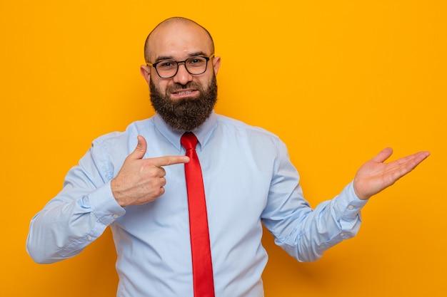 Bebaarde man in rode stropdas en blauw shirt met bril presenteren met arm van haar hand wijzend met wijsvinger naar de zijkant