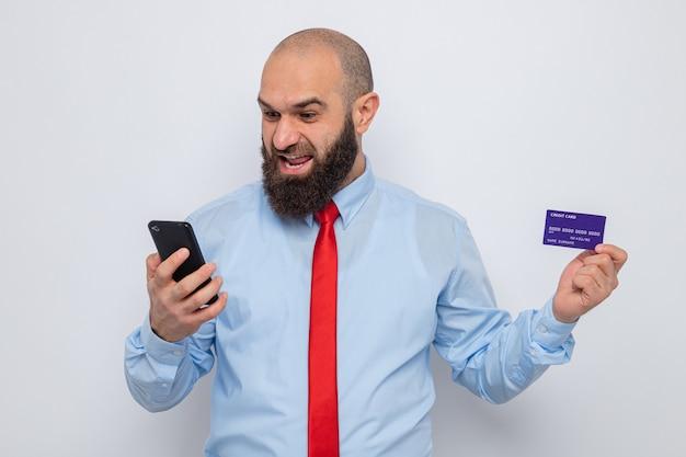 Bebaarde man in rode stropdas en blauw shirt met creditcard en smartphone die er blij en opgewonden naar kijkt en vrolijk lacht