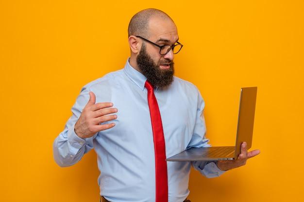 Bebaarde man in rode stropdas en blauw shirt met een bril die een laptop vasthoudt en er verbaasd en verbaasd naar kijkt terwijl hij over een oranje achtergrond staat
