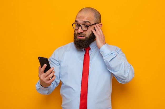 Bebaarde man in rode stropdas en blauw shirt met een bril die een smartphone vasthoudt en er verbaasd en verbaasd naar kijkt terwijl hij over een oranje achtergrond staat