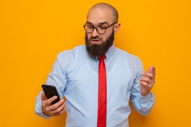 Bebaarde man in rode stropdas en blauw shirt met een bril die een smartphone vasthoudt en er verbaasd en verward naar kijkt