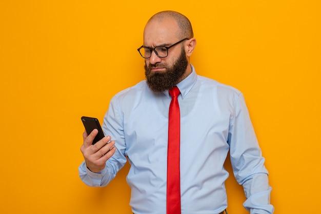 Bebaarde man in rode stropdas en blauw shirt met een bril die een smartphone vasthoudt en ernaar kijkt met een serieus gezicht