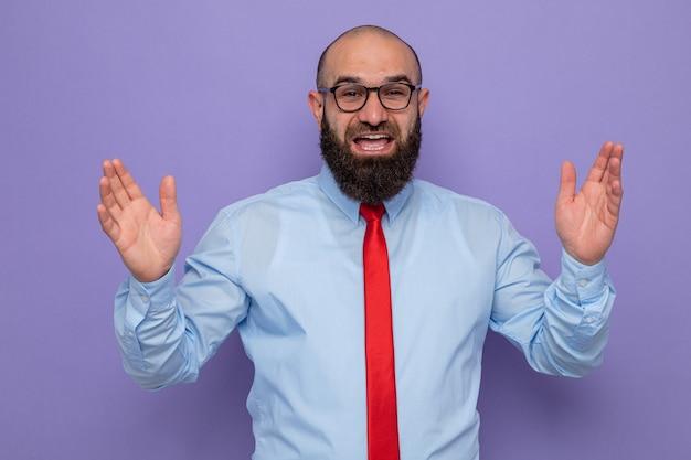 Bebaarde man in rode stropdas en blauw shirt met een bril die er blij en opgewonden uitziet en schreeuwend zijn handen opsteekt