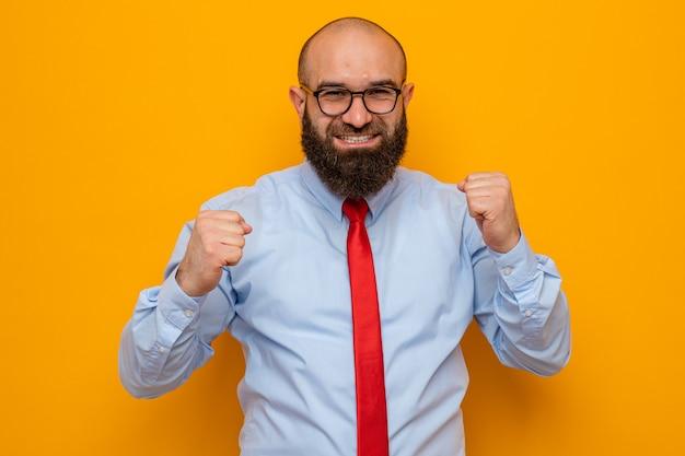 Bebaarde man in rode stropdas en blauw shirt met een bril die er blij en opgewonden uitziet met gebalde vuisten