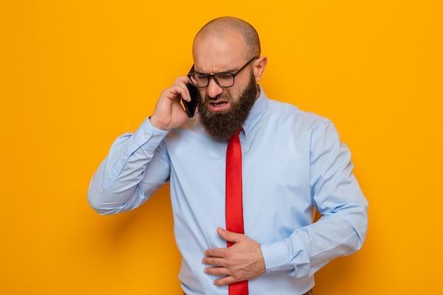 Bebaarde man in rode stropdas en blauw shirt met een bril die er onwel uitziet en zijn buik aanraakt terwijl hij op een mobiele telefoon praat die over een oranje achtergrond staat