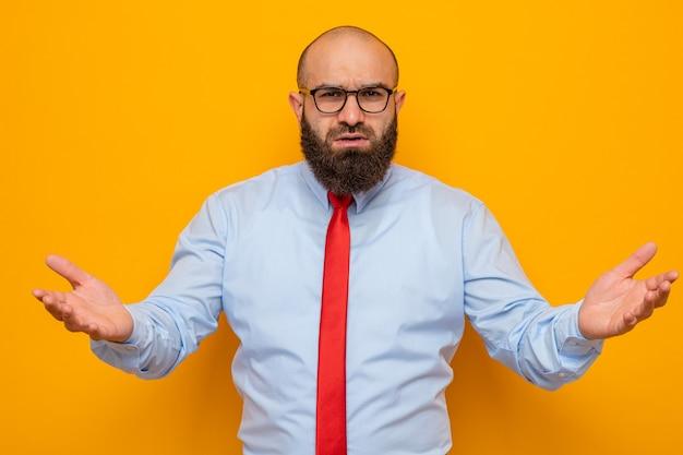 Bebaarde man in rode stropdas en blauw shirt met een bril die er verward uitziet en zijn armen naar de zijkanten spreidt