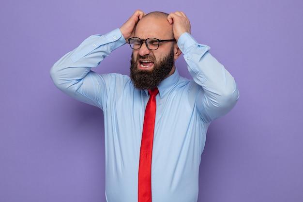 Bebaarde man in rode stropdas en blauw shirt met een bril die geïrriteerd en gefrustreerd schreeuwt en schreeuwt