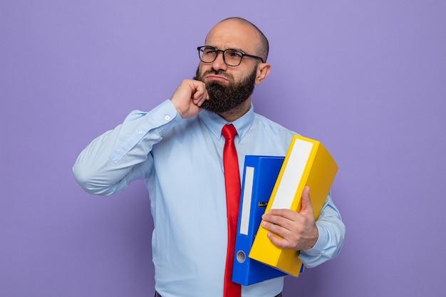 Bebaarde man in rode stropdas en blauw shirt met een bril die kantoormappen vasthoudt en verbaasd opkijkt terwijl hij over een paarse achtergrond staat