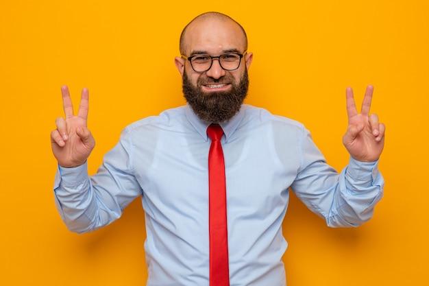 Bebaarde man in rode stropdas en blauw shirt met een bril die naar de camera kijkt en vrolijk glimlacht met een v-teken dat over een oranje achtergrond staat