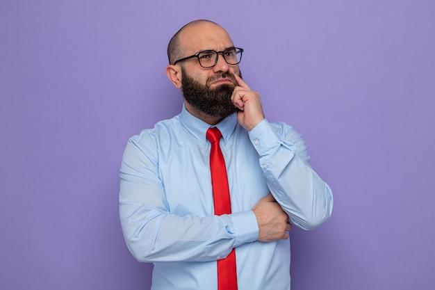Bebaarde man in rode stropdas en blauw shirt met een bril op die opzij kijkt verbaasd denken