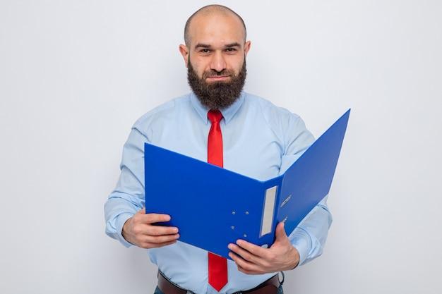 Bebaarde man in rode stropdas en blauw shirt met kantoormap kijkend naar camera met een glimlach op het gezicht, blij en zelfverzekerd over een witte achtergrond