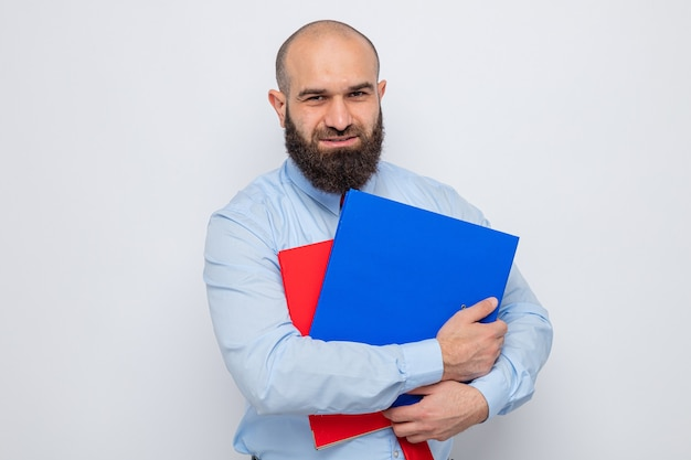 Bebaarde man in rode stropdas en blauw shirt met kantoormappen die naar de camera kijken met een glimlach op het gezicht op een witte achtergrond