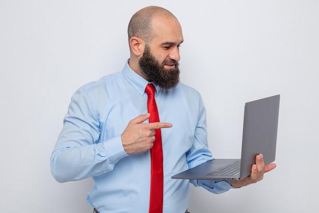 Bebaarde man in rode stropdas en blauw shirt met laptop wijzend met wijsvinger op het scherm van zijn laptop glimlachend vrolijk staande op witte achtergrond