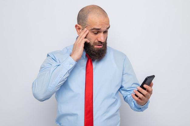 Bebaarde man in rode stropdas en blauw shirt met mobiele telefoon die er verbaasd en verrast naar kijkt