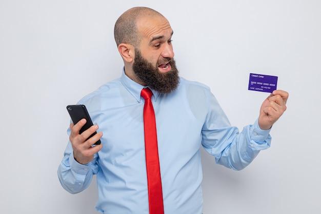 Bebaarde man in rode stropdas en blauw shirt met smartphone en creditcard die verbaasd en blij naar de kaart kijkt