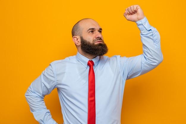 Bebaarde man in rode stropdas en overhemd opzij kijkend gelukkig en zelfverzekerd vuist opsteken als een winnaar