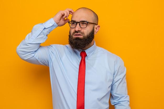 Bebaarde man in rode stropdas en shirt met bril opzij kijkend verbaasd op zijn hoofd krabben