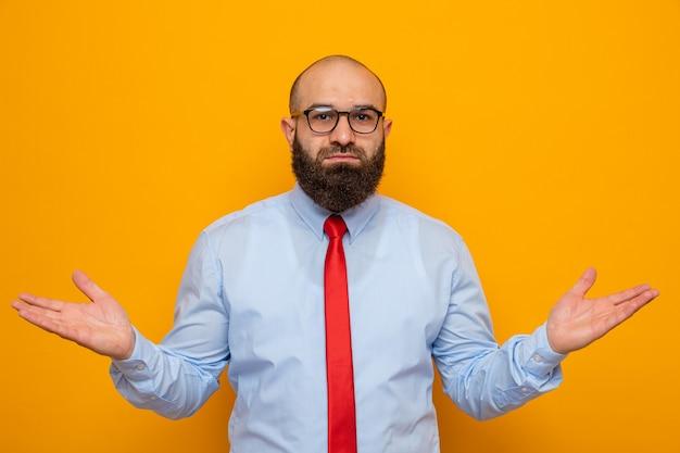 Bebaarde man in rode stropdas en shirt met een bril die er verward uitziet en amrs naar de zijkanten spreidt