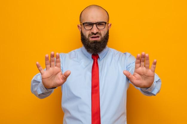 Bebaarde man in rode stropdas en shirt met een bril die er verward uitziet en een stopgebaar maakt met handen