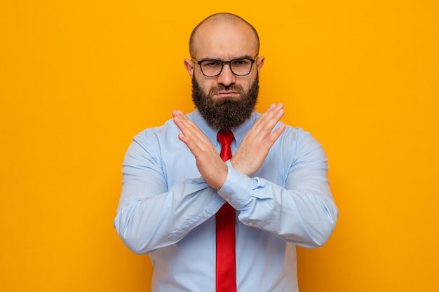 Bebaarde man in rode stropdas en shirt met een bril die met een serieus gezicht kijkt en een stopgebaar maakt met handen die de handen kruisen