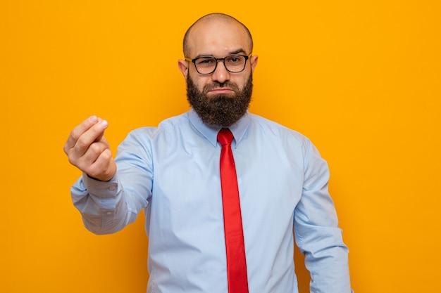 Bebaarde man in rode stropdas en shirt met een bril op zoek naar geldgebaar en wrijft over de vingers en ziet er zelfverzekerd uit