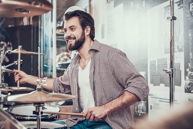 Bebaarde man in shirt speelt op drumstel.