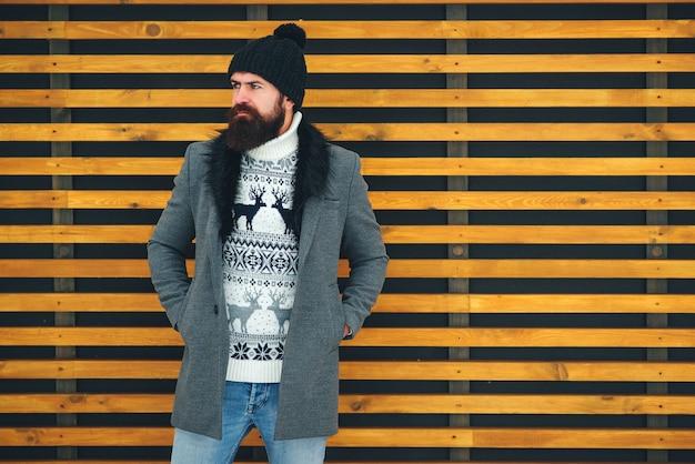 Bebaarde man in stijlvolle jas en zwarte hoed. outdoor portret van knappe man in winter outfit.