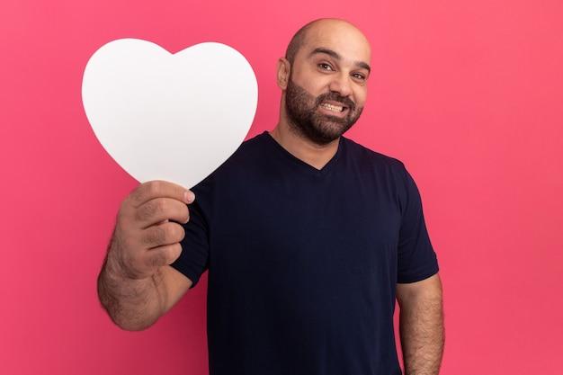 Bebaarde man in t-shirt met kartonnen hart glimlachend vrolijk staande over roze muur