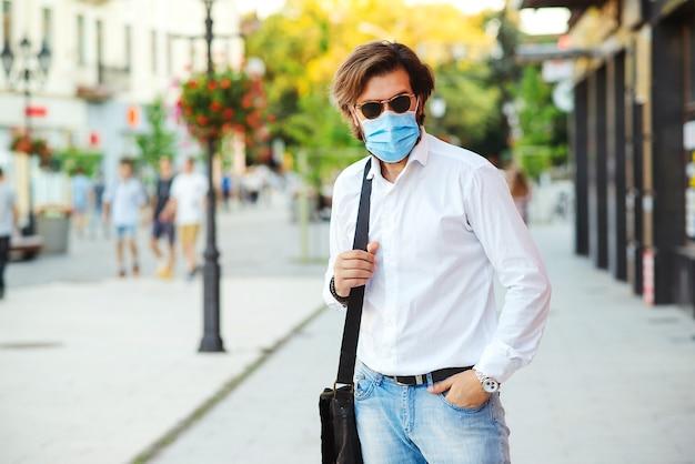 Bebaarde man in veiligheidsmasker op straat. knappe man met medisch masker na het werk tijdens quarantaine.
