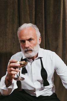 Bebaarde man in wit overhemd die in de camera kijkt en martiniglas vasthoudt