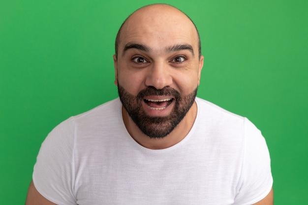 Bebaarde man in wit t-shirt blij en opgewonden glimlachend vrolijk staande over groene muur