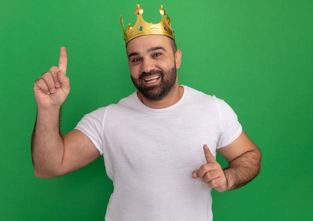 Bebaarde man in wit t-shirt met gouden kroon blij en positief wijzend met wijsvingers staande over groene muur