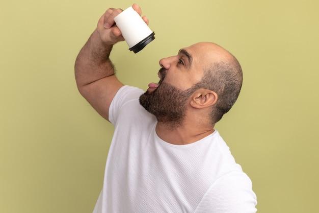Bebaarde man in wit t-shirt met koffiekopje gaan drinken staande over groene muur