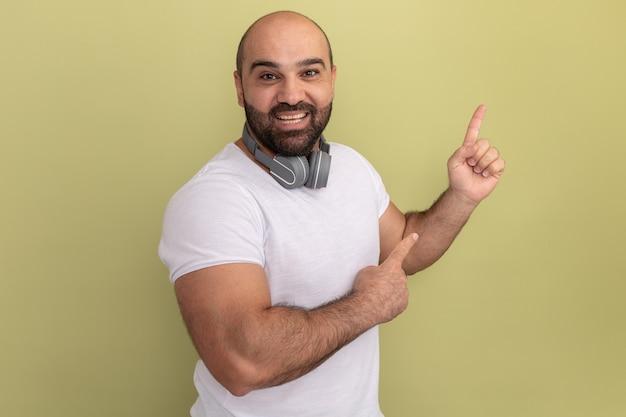 Bebaarde man in wit t-shirt met koptelefoon blij en positief wijzend met wijsvingers naar de zijkant staande over groene muur