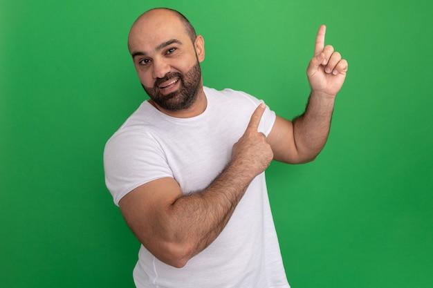 Bebaarde man in wit t-shirt met smie op gezicht wijzend met wijsvingers naar de zijkant glimlachend vrolijk staande over groene muur