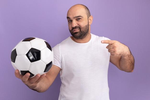 Bebaarde man in wit t-shirt met voetbal met zelfverzekerde uitdrukking wijzend met wijsvinger naar de zijkant staande over paarse muur