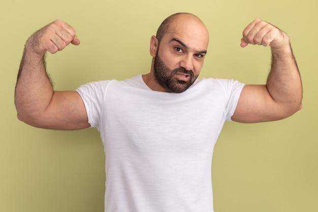 Bebaarde man in wit t-shirt met zelfverzekerde uitdrukking, vuisten als een winnaar die over groene muur staat